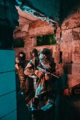 Fotografie paintball tým v jednotné a ochranné masky hrát paintball zbraně značky v opuštěné budově