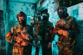 Fotografia squadra di paintball in maschere protettive e uniforme in piedi con le pistole di paintball in costruzione abbandonata