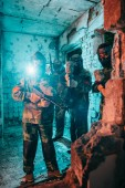paintball tým v jednotné a ochranné masky s paintball zbraně v opuštěné budově