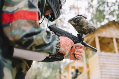partial view of male paintball player in goggle mask and camouflage with paintball gun outdoors