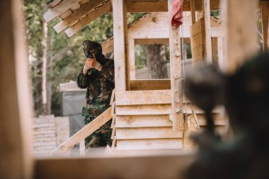 Selective focus of male paintball player in goggle mask and camouflage aiming by paintball gun on wooden tower stock vector