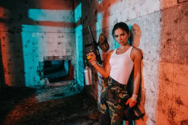 confident young female paintballer in camouflage and white singlet holding marker gun in abandoned building