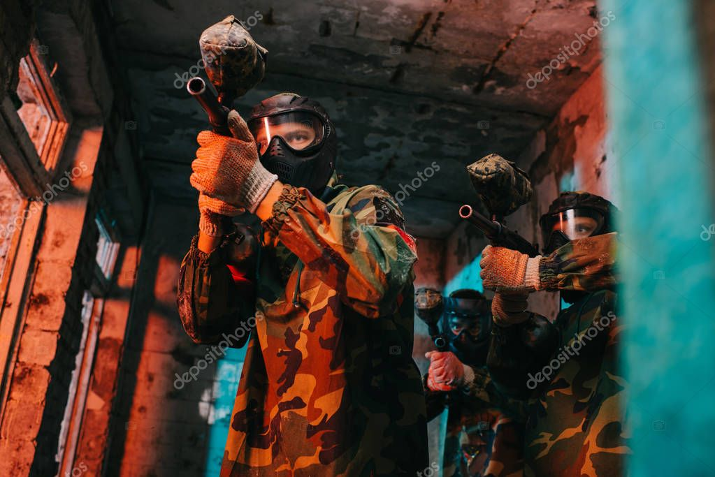 Low angle view of paintball team in uniform and protective masks aiming by paintball guns in abandoned building stock vector