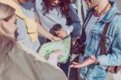 Fotografie částečný pohled mladých přátel hledá cíl na mapě společně na cestách