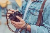 Fotografie Oříznout záběr turista s fotoaparátem v ruce