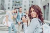 Fotografie atraktivní tmavovláska s fotoaparátem v městě s přáteli