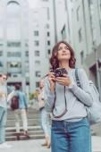 Fotografia ragazza attraente con la macchina fotografica a piedi in città urbana con gli amici