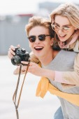 Fotografia turistica sorridente che dà sul dorso alla felice amica mentre lei prendendo foto sulla macchina fotografica