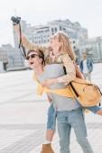 Fotografia ragazzo eccitato trasporta sulle spalle la ragazza mentre lei prendendo foto sulla macchina fotografica