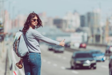 young woman with backpack and coffee to go hitchhiking at road