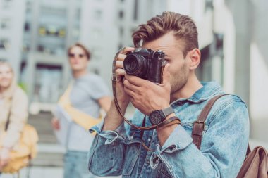 selective focus of man taking picture on photo camera of new city during journey