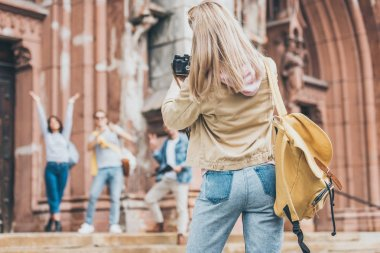 blonde woman taking photo of tourists on camera in city
