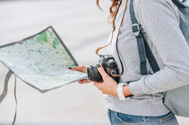 cropped view of traveler holding photo camera and map in city