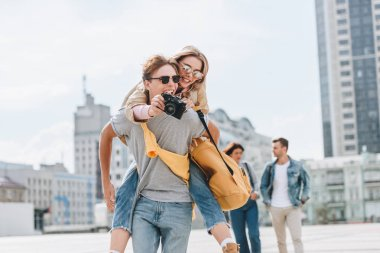 happy boyfriend giving piggyback to girlfriend with photo camera in city with friends behind