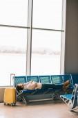 mladý muž ležící na sedadlech při čekání na let v letištní terminál