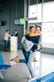vidám fiatal pár átölelve a repülőtér utas
