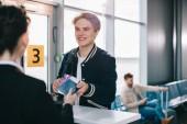 Oříznout záběr usmívajícího se muže dávat pas letištnímu personálu