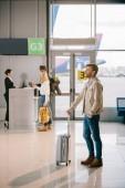 boční pohled na usmívající se mladík stál s kufrem v Letiště