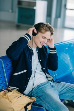 smiling young man in headphones sitting and waiting for flight in airport
