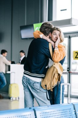 emotional young couple hugging and girl crying in airport terminal