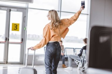 back view of happy young woman holding passport and suitcase in airport