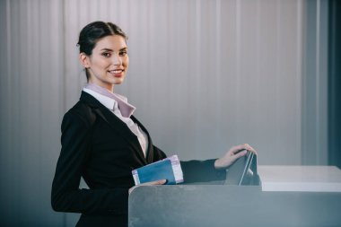 young female worker smiling at camera while working at check-in desk in airport