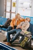 Fotografie pohled z vysokého úhlu nudit mladých lidí čeká na let v letištní terminál