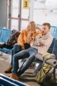 vysoký úhel pohled znuděný mladý pár čeká na let v Letiště