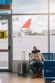 Fotografie mladý muž spí při čekání na let v Letiště