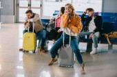 Fotografie znuděný mladých lidí se zavazadly čekání na let v letištní terminál