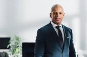 portrét pohledný mladý afroamerické podnikatel se usmívá na kameru v úřadu