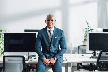 handsome young african american businessman sitting and smiling at camera in open space office