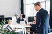 Fényképek súlyos fiatal üzletember használ laptop és látszó-on hivatal munkatársai