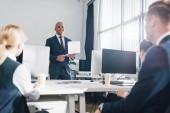 nízký úhel pohledu usmívající se mladý americký podnikatel držení notebooku a při pohledu na kolegy v kanceláři