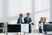 emocionální mladý podnikatel mluví s kolegy na pracovišti