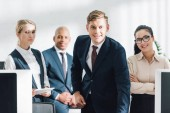 confident professional young multiethnic business people smiling at camera in office