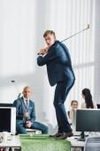 mladý podnikatel, hraje golf a spolupracovníky seděla v kanceláři
