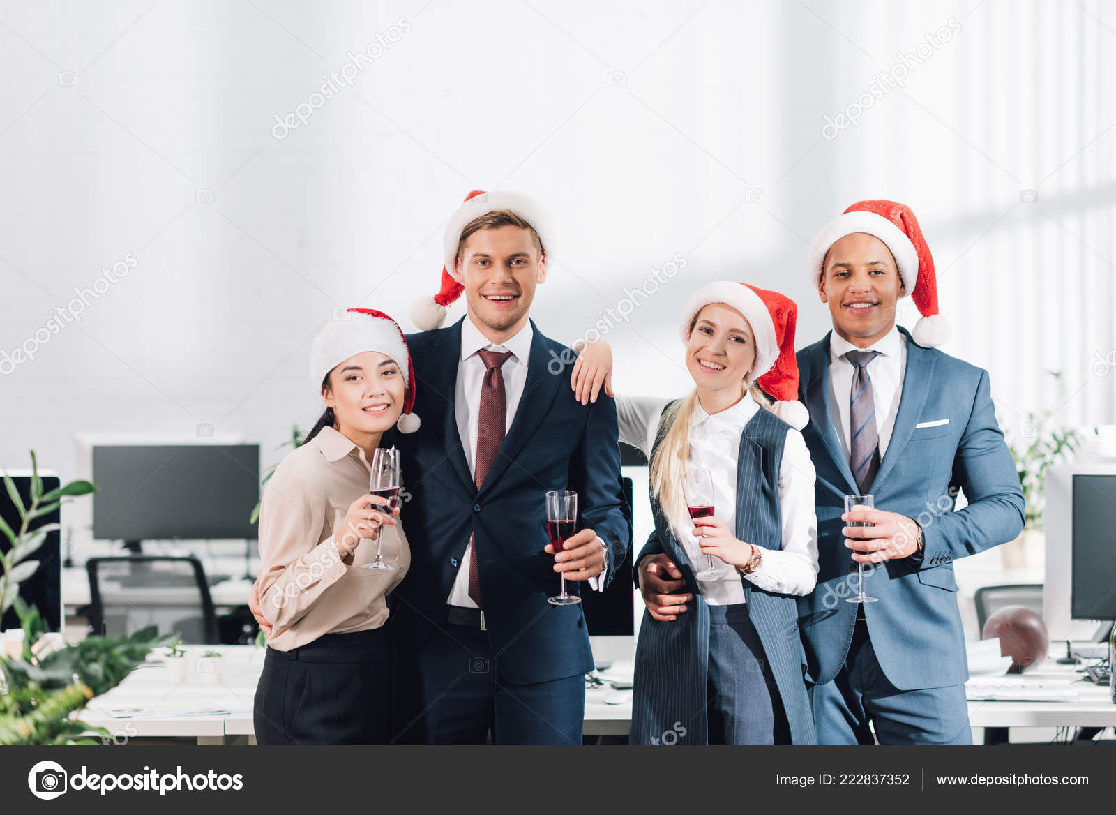 happy young colleagues santa hats drinking champagne smiling camera