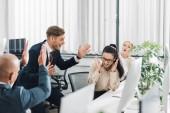 nadšený mladý se spolupracovníky slaví dobré zprávy v kanceláři