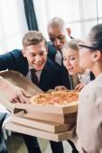 felice giovane colleghe guardando gustosa pizza in ufficio