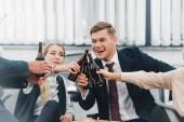 oříznuté snímek šťastné mladé spolupracovníky cinkání lahví piva v úřadu