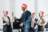 Fotografie happy young multiracial business colleagues in santa hats celebrating christmas in office