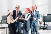 Fotografie smiling young business colleagues in santa hats drinking wine and celebrating christmas in office