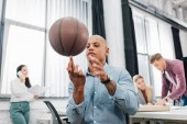 Fotografie nízký úhel pohledu mladého afroamerické muže hrát s míčem basketbal v úřadu