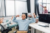 Fotografie happy young african american man showing biceps and smiling at camera while colleagues having fun behind in office