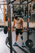 sportovní mladého sportovce s umělou nohou cvičit s činka v posilovně