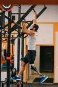 Fényképek handsome young sportsman with artificial leg working out with gymnastics ladder at gym