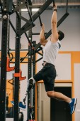 Fényképek athletic young sportsman with artificial leg working out with gymnastics ladder at gym