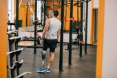 Photo handsome young sportsman with artificial leg standing near gymnastics ladder at gym