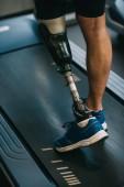 ritagliata colpo dello sportsman con gamba artificiale camminare sul tapis roulant in palestra